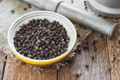 Bowl of black pepper on wooden table Stock Image