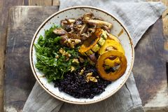 Black rice with roasted delicata squash, massaged kale and shiitake mushrooms. Bowl of black rice with roasted delicata squash, massaged kale and shiitake Stock Photography