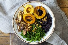 Black rice with roasted delicata squash, massaged kale and shiitake mushrooms. Bowl of black rice with roasted delicata squash, massaged kale and shiitake Stock Photo