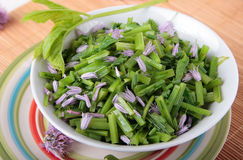 Bowl of blanched goutweed salad with chive flowers Stock Photos