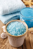 Bowl of blue sea salt and other spa cosmetics on rustic wood Royalty Free Stock Images