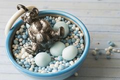 Bowl with blue and white aniseed balls, Dutch muisjes, with silver bear rattle. royalty free stock photography