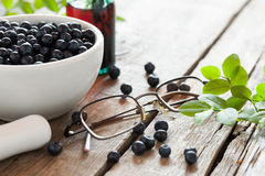 Bowl with  blueberries, glasses and bottle of tincture Royalty Free Stock Photography