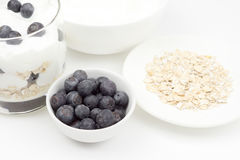 A bowl of blueberries next to a bowl of oatmeal, yogurt and a gl Royalty Free Stock Photo