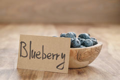 Bowl with blueberries with paper card on wood table Royalty Free Stock Image