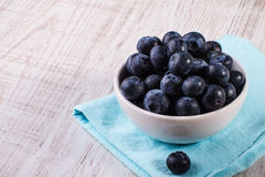 Bowl of blueberries. White bowl of blueberries on wooden table Stock Photography