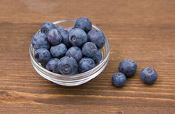 Bowl with blueberries on wood Stock Images