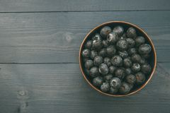 Bowl of blueberries on wood table with copy space Royalty Free Stock Photos