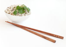 Bowl with boiled rice and chopsticks near. White ceramic bowl with boiled rice and wooden chopsticks isolated on white Stock Photos