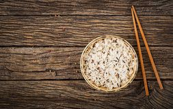 Bowl with boiled rice on a wooden background. Vegan food. Stock Photo