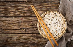 Bowl with boiled rice on a wooden background. Vegan food. Stock Photos