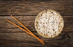 Bowl with boiled rice on a wooden background. Royalty Free Stock Images