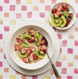 Bowl of Breakfast Cereal and Fruit. A white bowl of breakfast cereal topped with sliced strawberries and kiwi fruit on a patterned placemat Royalty Free Stock Photography