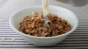 Bowl of breakfast cereal with skim milk being added stock video