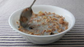 Bowl of breakfast cereal with skim milk being stirred and eaten stock video footage