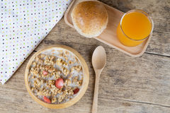 Bowl of breakfast muesli with oat and wheat flakes mixed with dried fruit and nuts in a wooden  bowl. Stock Photos