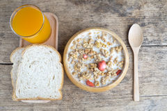 Bowl of breakfast muesli with oat and wheat flakes mixed with dried fruit and nuts in a wooden  bowl. Stock Image
