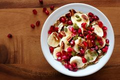Bowl of breakfast oatmeal with pomegranate, bananas, seeds and nuts Stock Images
