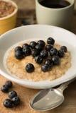 Bowl of Breakfast Porridge and Blueberries on Wooden Background Stock Images