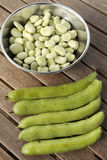 Bowl of broad beans and pods. On garden table Stock Photo