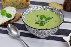 Bowl of broccoli cream soup, grain bread with pumpkin seeds and spoon on the table, healthy vegetarian eating concept. Balanced di. Bowl of broccoli cream soup royalty free stock photography