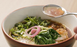 Bowl with broth, shrimp and fesh parsley Stock Images