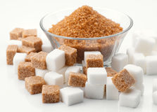 Bowl of brown sugar and sugar cubes surround Royalty Free Stock Photos