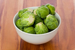 Bowl of Brussel Sprouts. A small white bowl of brussel sprouts against a wooden background royalty free stock image