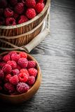 Bowl and bucket with fresh raspberries on wooden board.  Royalty Free Stock Images