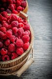 Bowl and bucket with juicy raspberries on wooden board.  Royalty Free Stock Images