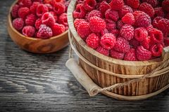 Bowl and bucket with raspberries on wooden board.  Royalty Free Stock Photos
