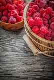 Bowl and bucket with red raspberries on wooden board.  Stock Photos