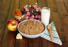 Bowl buckwheat cereal,  glass  milk,  apple, nuts  on dark wood. Royalty Free Stock Photo