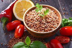 Bowl of buckwheat kasha on wooden table Royalty Free Stock Images