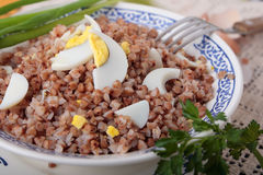 Bowl of buckwheat porridge with sliced boiled eggs Stock Photography
