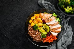 Bowl Buddha. Buckwheat, pumpkin, chicken fillet, avocado, carrots. On a black background. Top view. Free space for your text stock images