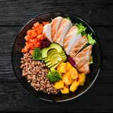 Bowl Buddha. Buckwheat, pumpkin, chicken fillet, avocado, carrots. On a black background. Top view. Free space for your text stock image