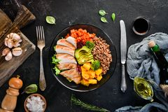 Bowl Buddha. Buckwheat, pumpkin, chicken fillet, avocado, carrots. On a black background. Top view. Free space for your text royalty free stock photo