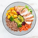 Bowl Buddha. Buckwheat, pumpkin, chicken fillet, avocado, carrots. On a white wooden background. Top view. Free space for your text stock image