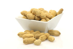 Bowl with a bunch of peanuts. In and around it Stock Image