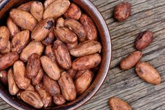 Bowl with cacao beans on table royalty free stock image