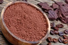 Bowl with cacao powder with coffee beans and dark chocolate. On table stock photo