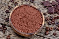 Bowl with cacao powder and coffee beans on rustic table. Bowl with cacao powder and coffee beans on rustic wooden table stock images