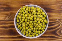 Bowl with canned green peas  on wooden table. Top view stock photo