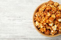 Bowl with caramel popcorn on white wooden background. Top view. Space for text stock images