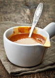 Bowl of caramel sauce. Bowl of melted caramel sauce on old wooden table royalty free stock image