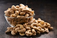Bowl with cashew nuts on wooden table Stock Photo