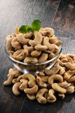 Bowl with cashew nuts on wooden table Stock Image