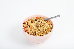 Bowl of cereal. A pink bowl of cereal with a spoonin it stock images