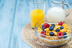 Bowl of cereal with berries, glass of orange juice and jug of milk. On a light blue wooden background Stock Image